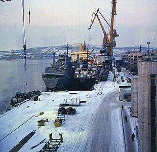 "Atomflot Base. Service ship unloading submarine fuel to railway wagons. In the background is the nuclear powered icebreaker ""Sibyr""."